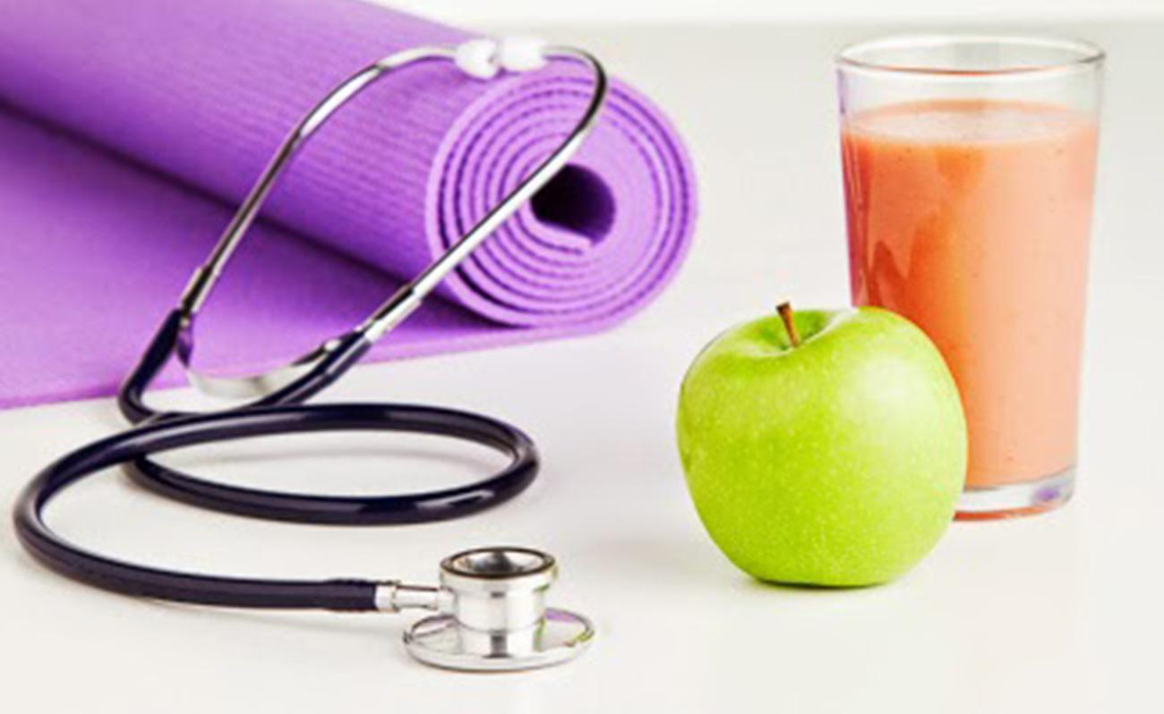 Apple, smoothie, stethoscope and yoga mat